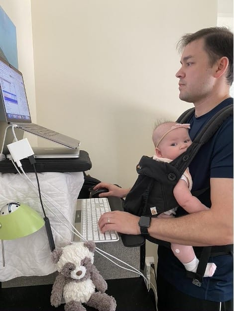 Ryan Brelje at his standing desk with his daughter strapped to his chest